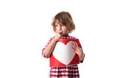 Enfant drôle de fille dans la robe rouge de plaid avec une feuille avec un coeur, Co Photographie stock