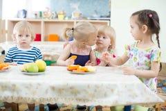 Enfant drôle embrassant un autre au centre de soins de jour Photo libre de droits