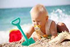 Enfant drôle jouant sur la plage Photos stock