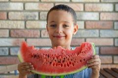 Enfant drôle mangeant la pastèque à l'intérieur, foyer sur des yeux Photos libres de droits
