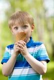Enfant drôle mangeant une crême glacée savoureuse à l'extérieur Images libres de droits