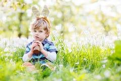 Enfant drôle utilisant des oreilles de lapin de Pâques et mangeant du chocolat au PS Image libre de droits
