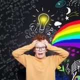 Enfant effrayé avec l'ampoule Concept d'éducation, de séance de réflexion et d'idée Garçon roux mignon d'étudiant sur le fond de  photo libre de droits