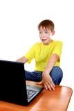 Enfant effrayé avec l'ordinateur portable photographie stock