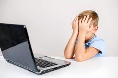 Enfant effrayé couvrant son visage au bureau d'ordinateur portable Images stock