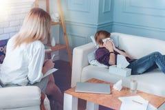Enfant effrayé pleurant tout en parlant avec le psychothérapeute photo libre de droits