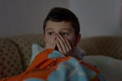 Enfant effray? observant le film effrayant ? la TV, se reposant sur le divan la nuit image libre de droits