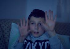 Enfant effray? observant le film effrayant ? la TV, se reposant sur le divan la nuit photographie stock libre de droits