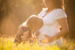 Enfant embrassant la mère enceinte d'og de ventre Images libres de droits