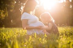 Enfant embrassant la mère enceinte d'og de ventre Image stock