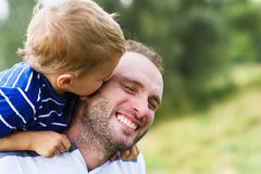 Enfant embrassant le père Image libre de droits