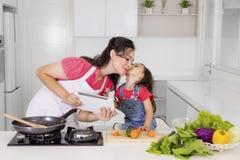 Enfant embrassant sa mère dans la cuisine Image libre de droits