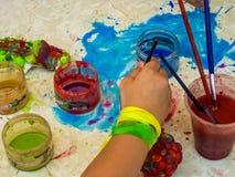 Enfant employant le pinceau et avec des approvisionnements de peinture et faisant un d?sordre images stock