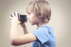 Enfant employant les verres noirs de carton de 3D VR photos stock