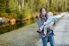 Enfant en bas âge adorable dans des mains de mères Photographie stock