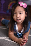 Enfant en bas âge asiatique féminin s'étendant sur le plancher souriant à l'appareil-photo Image libre de droits