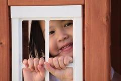 Enfant en bas âge asiatique souriant par la fenêtre de maison de théâtre Photo stock