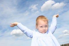Enfant en bas âge avec des bras dans le ciel. Photo stock