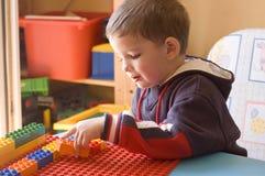 Enfant en bas âge avec des jouets dans sa chambre Images libres de droits