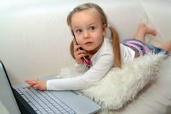 Enfant en bas âge avec l'ordinateur portatif et le téléphone Image stock