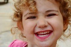 Enfant en bas âge avec la crème glacée sur son visage et une expression d'amusement Photos libres de droits