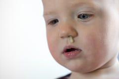 Enfant en bas âge avec la morve accrochant hors du nez Photos stock
