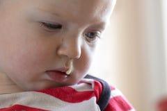 Enfant en bas âge avec la morve accrochant hors du nez Images libres de droits