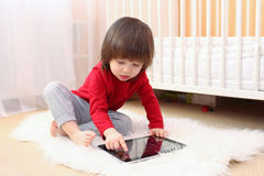 Enfant en bas âge avec la tablette à la maison Image stock