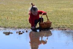 Enfant en bas âge avec le manteau rouge se mettant à genoux à la réflexion de l'eau image libre de droits