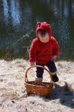Enfant en bas âge avec le manteau rouge se reposant devant l'étang avec le panier image stock
