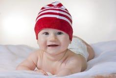 Enfant en bas âge avec le mensonge rouge de chapeau Images stock