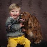 Enfant en bas âge avec son chien Photos libres de droits
