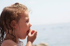 Enfant en bas âge ayant un casse-croûte et appréciant la vue de plage photographie stock