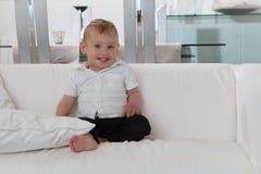 Enfant en bas âge bien comporté heureux s'asseyant à la maison image libre de droits