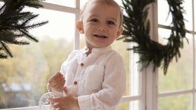 Enfant en bas âge blond adorable dans la chemise blanche se tenant sur le filon-couche de fenêtre tenant un jouet et un sourire d banque de vidéos