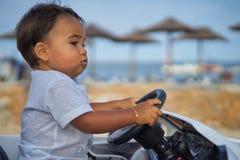 Enfant en bas âge conduisant la voiture par la plage Photographie stock libre de droits