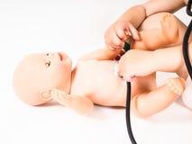 Enfant en bas âge courant un contrôle de santé sur une poupée chauve Image libre de droits