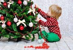 Enfant en bas âge décorant l'arbre de Noël photographie stock
