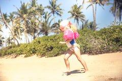 Enfant en bas âge d'enfant courant dans les vêtements de bain sur la plage avec la lumière du soleil lumineuse pendant le mode de image libre de droits
