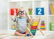 Enfant en bas âge d'enfant avec des lunettes jouant l'abaque Image stock