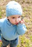 Enfant en bas âge dans parler bleu au-dessus du téléphone Photographie stock