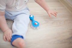 Enfant en bas âge de bébé garçon s'asseyant et jouant avec le jouet Images stock