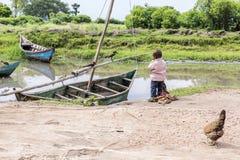 Enfant en bas âge de canoë et d'oiseaux de observation de village de pêche Images stock