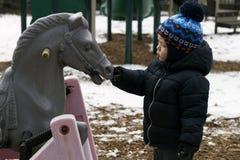 Enfant en bas âge de deux ans jouant avec un cheval de jouet Enfant alimentant le cheval en bois photo stock