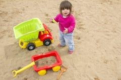 Enfant en bas âge de fille jouant avec le camion dans le bac à sable Image libre de droits
