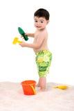 Enfant en bas âge de garçon de plage avec des jouets dans le sable Photo stock
