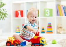 Enfant en bas âge de petit garçon jouant avec la voiture de jouet Images stock
