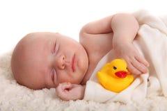 Enfant en bas âge de sommeil avec un Duckie en caoutchouc sur le blanc Image stock