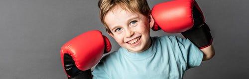 Enfant en bas âge de sourire avec les cheveux rouges avec de grands gants de boxe Photographie stock