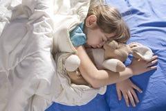 Enfant en bas âge dormant avec ses lièvres Image stock